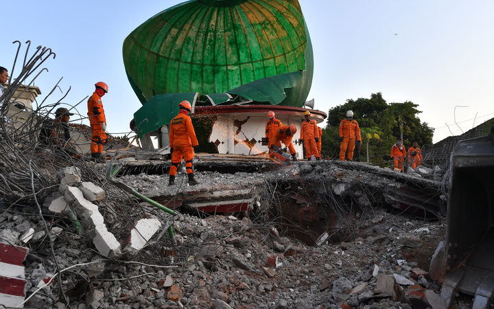 Indonesian search and rescue personnel work on a collapsed mosque in Pemenang.