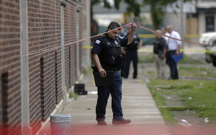 Chicago Police officers and detectives investigate a shooting where multiple people were shot over the weekend in Chicago Illinois