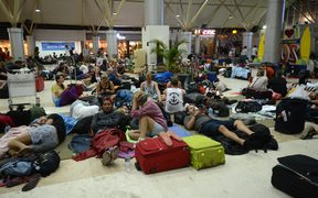Foreign tourists sleep on the floor as they wait to depart from the Praya Lombok International Airport as aftershocks continue to rock Indonesia.