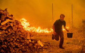 Alex Schenck, 15, carries a water bucket while fighting to save his home as the Ranch Fire tears down New Long Valley Rd in California.