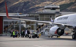 Passengers board commercial jet at Queenstown Airport.