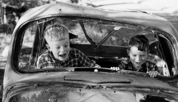 Two boys playing in wrecked car, 1957, North Island, by Eric Lee-Johnson.