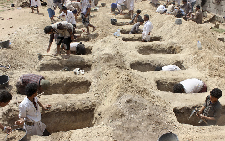 Yemenis dig graves for children who where killed when their bus was hit during a Saudi-led coalition air strike that targeted the Dahyan market the previous day in the Huthi rebels stronghold province of Saada
