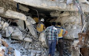Syrian civil defense members conduct search and rescue operations at wreckage of a building after a blast in Idlib, Syria.