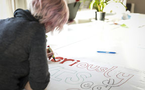 Principal Traci Liddall at South Wellington Intermediate School prepares a banner for the teachers strike.
