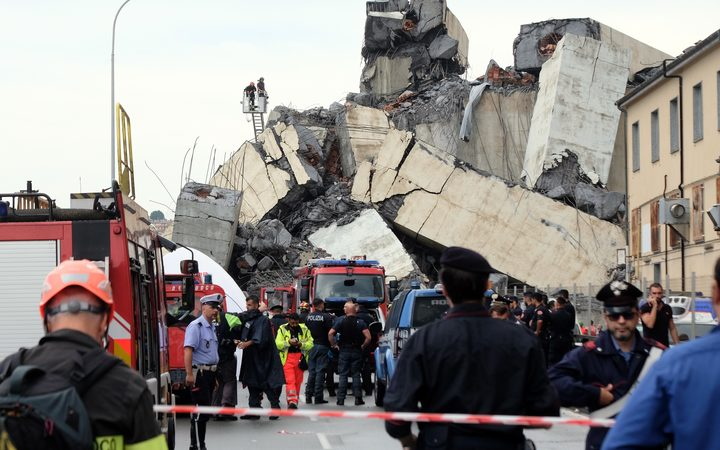 Rescuers are at work amid the rubble of a section of the Morandi motorway bridge that collapsed.