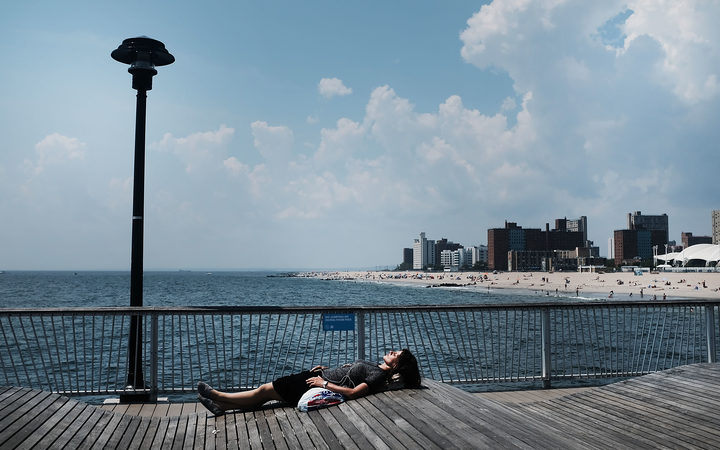 A woman lays along the boardwalk at Coney Island on a hot summer afternoon on August 7, 2018 in New York City.