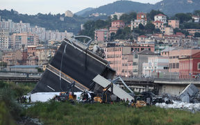 Rescuers inspect the rubble and wreckages by the Morandi motorway bridge after a section collapsed in Genoa.