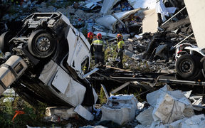 Rescuers inspect the rubble and wreckages by the Morandi motorway bridge.