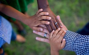 The way we see the world is informed by values inherent in our culture and environment. Different race kids holding hands.