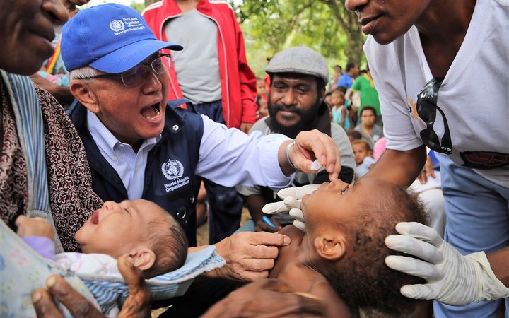 The WHO's Regional Director for the Pacific, Dr Shin Young-soo provides oral polio vaccine in Lae in Morobe