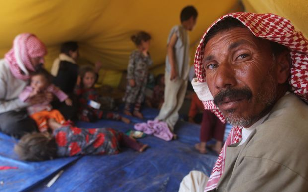 Iraqi Yazidi refugees rest inside a tent at the Newroz camp in Hasaka province, north eastern Syria.