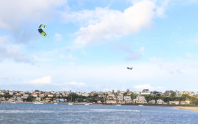A kitesurfer catches some big air at Sandspit