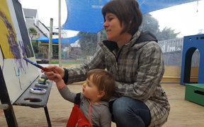 Fiona Roberton helps her daughter Kate (17-months) paint at Newtown Playcentre.