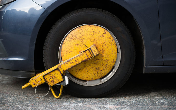 Car wheel blocked by wheel lock due to illegal parking violation