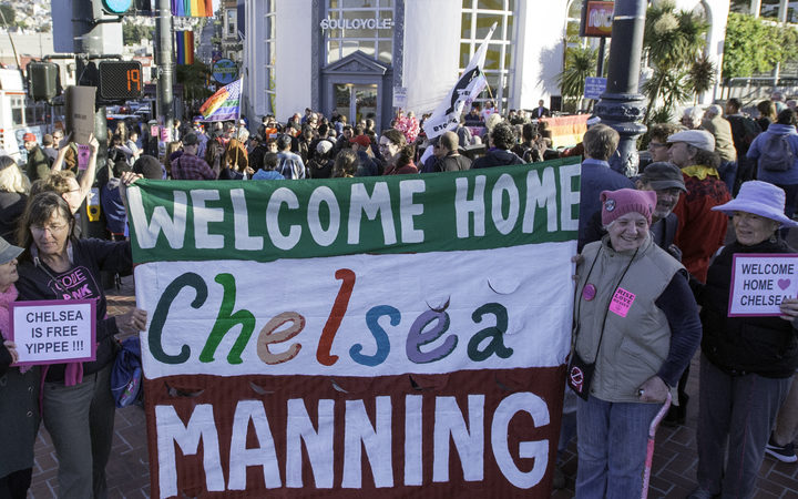 People cheer and hold up signs showing support for Chelsea Manning in the Castro District of San Francisco, California in 2017, during a celebration for her release.