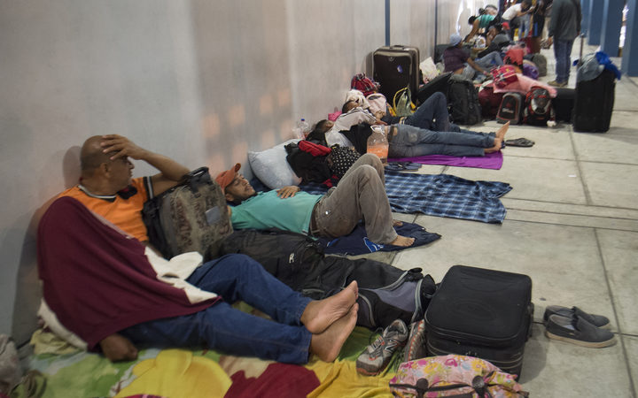 Venezuelan nationals spend the night sleeping on the sidewalk at the binational border attention centre (CEBAF) in Tumbes, northern Peru on August 24, 2018.