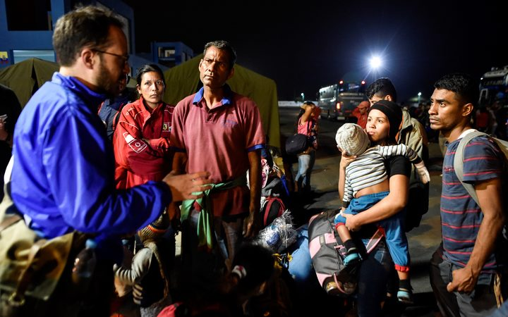 An official of UNHCR speaks with Venezuelan migrants on August 25, 2018, upon their arrival in Huaquillas.