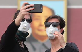 Foreign tourists wearing face masks against air pollution visit the Tian'anmen Square in heavy smog in, China.