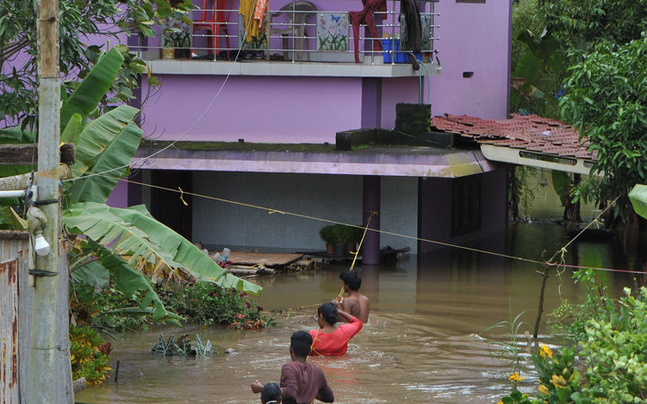 Residents wade through flood waters to their marooned houses