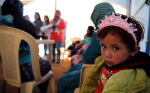 A child sits under a tent with Syrian refugee women attending a class on family planning organised by Doctors Without Borders (MSF) at a makeshift camp by Taybeh village, in Lebanon's eastern Bekaa Valley, on November 15, 2015.