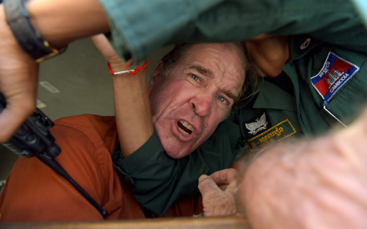 Australian filmmaker James Ricketson reacts as he attempts to speak to journalists from a prison vehicle after his verdict at the Phnom Penh court.