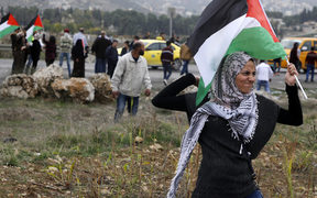 A Palestinian protester waves a Palestinian flag as she throws a stone during clashes with Israeli security forces near the Huwara checkpoint in the West Bank on Wednesday.