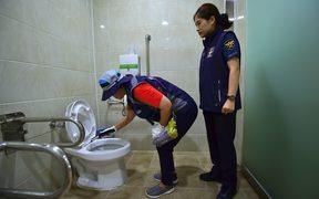 "A member of Seoul city's ""hidden camera-hunting"" squad and a policewoman inspect a women's bathroom stall to find a ""secret camera"" at a museum in Seoul."