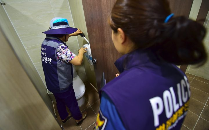 "This picture taken on August 18, 2016 shows a member of Seoul city's ""hidden camera-hunting"" squad (L) and a policewoman (R) inspecting a women's bathroom stall to find ""secret camera"" at a museum in Seoul."