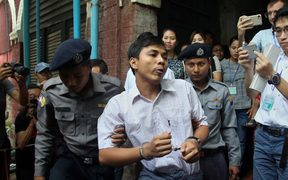 Detained Myanmar journalist Kyaw Soe Oo is escorted by police to a court.