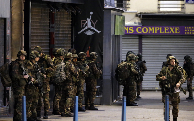 French army soldiers stand in position in the northern Paris suburb of Saint-Denis city center, on November 18, 2015, as French Police special forces raid an appartment, hunting those behind the attacks that claimed 129 lives in the French capital five days ago.