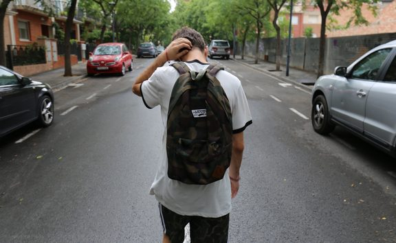 teenage boy with backpack on street