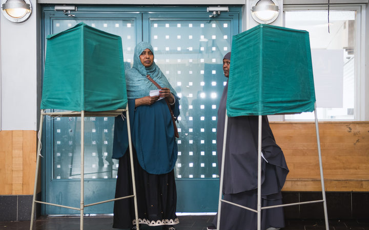 People stand on booths at a polling station during the Swedish general elections in the suburb of Rinkeby, north of Stockholm.