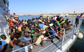 Illegal migrants from Africa sit on a Libyan coastguard boat as they arrive at a naval base in Tripoli after being rescued in the Mediterranean Sea, off the Libyan coast.