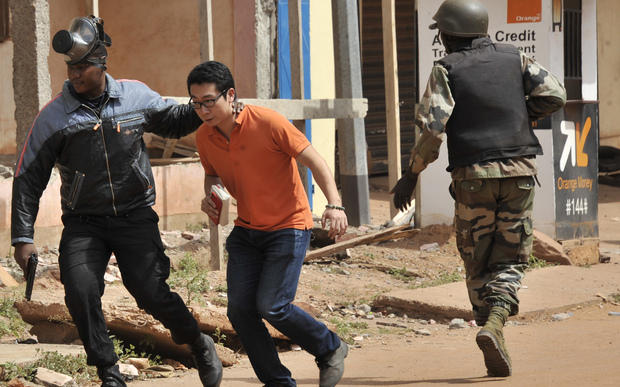 Malian security forces evacuate a man from an area surrounding the Radisson Blu hotel in Bamako