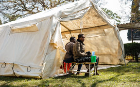 Cholera patients wait for treatment outside a tent during a visit of Zimbabwe Minister of Health, at the cholera treatment centre of the Beatrice Infectious Diseases Hospital, in Harare, on September 11, 2018.