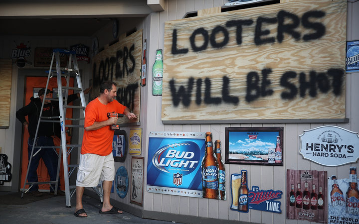 Doug Lewis and Chris Williams use plywood with the words'Looters will be shot to cover the windows of Knuckleheads bar as they try to protect the business ahead of the arrival of Hurricane Florence