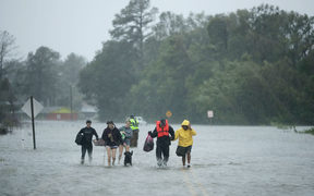 Volunteers from the Civilian Crisis Response Team help people to higher ground after rescuing them from their flooded homes during Hurricane Florence in James City, North Carolina.