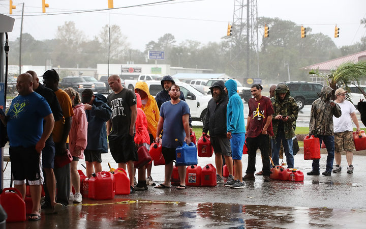 People wait in line to fill up their gas cans at a gas station that was damaged when Hurricane Florence hit Wilmington, North Carolina.
