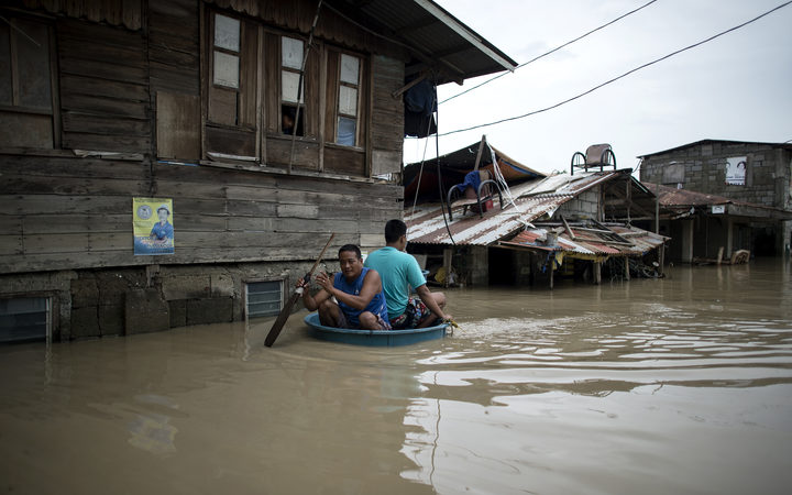 Men use a basin to cross a flooded street in the aftermath of Super Typhoon Mangkhut at Salonga Compound in Calumpit, Bulacan on September 16, 2018.