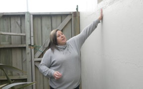 Business owner, Jennifer Rush, examines the patched-up cracks in her shop's exterior walls.