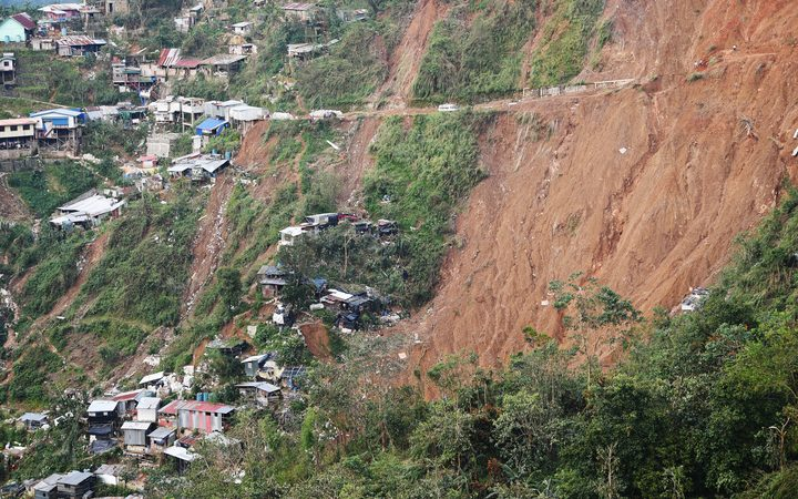 Philippine rescuers used shovels and their bare hands to claw through mounds of rocky soil, as they desperately looked for dozens of miners feared buried beneath a landslide unleashed by Typhoon Mangkhut.