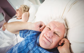 Senior man covers ears while wife snores