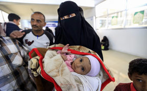 A Yemeni woman carries an ill child.