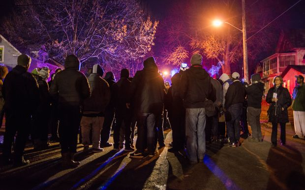 A group gathers in front of a police line after 5 people were shot at a Black Lives Matters protest November 24, 2015 in Minneapolis, Minnesota.