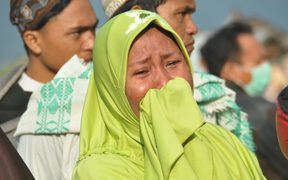 A woman cries as people look at the damages after an earthquake and a tsunami hit Palu, on Sulawesi Island.
