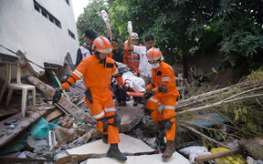 Rescue personnel evacuate earthquake survivor Ida, a food vendor, from the rubble of a collapsed restaurant in Palu, Indonesia's Central Sulawesi.