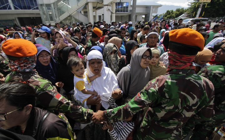 Residents queue to board a Hercules aircraft belonging to the Indonesian Air Force, as they are being evacuated after the earthquake and tsunami that hit the city.