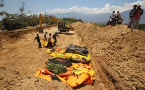 Officers bring the bodies of victims of the earthquake and tsunami to bury them in Palaroa village, in the city of Palu, Central Sulawesi, Indonesia.