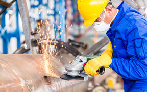 Industrial worker in manufacturing plant grinding to finish a pipeline.